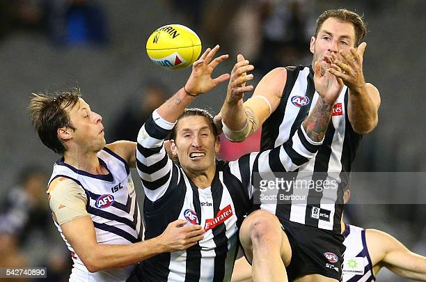 Travis Cloke of the Magpies and Jesse White of the Magpies compete for the ball with Cameron Sutcliffe of the Dockers during the round 14 AFL match...