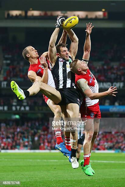 Travis Cloke of the Magpies is challenged by Ted Richards of the Swans and Daniel Hannebery of the Swans during the round 20 AFL match between the...