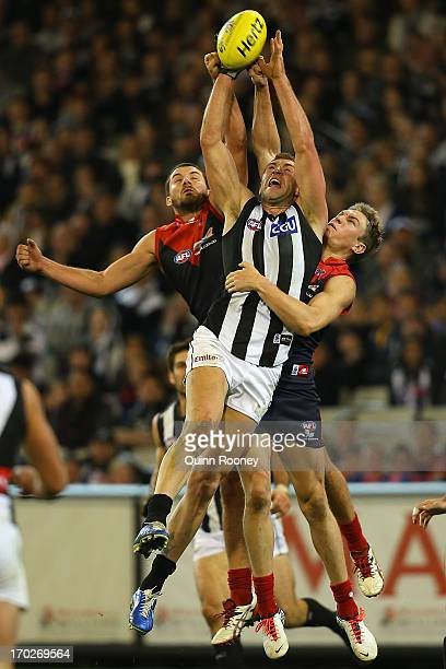 Travis Cloke of the Magpies marks infront of Colin Garland and Tom McDonald of the Demons during the round 11 AFL match between the Melbourne Demons...