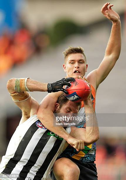 Travis Cloke of the Magpies marks the ball over Adam Tomlinson of the Giants during the round 16 AFL match between the Greater Western Sydney Giants...