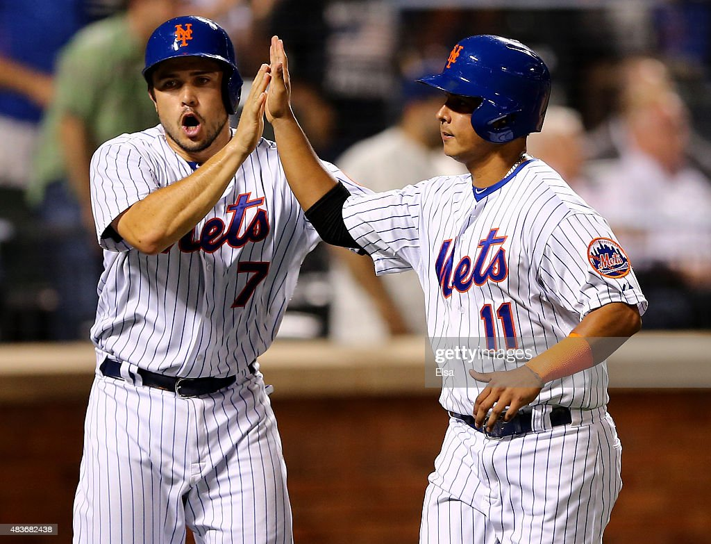 Travis d'Arnaud #7 and Ruben Tejada #11 of the New York Mets celebrate after they scored in the eighth inning against the Colorado Rockies on August 11, 2015 at Citi Field in the Flushing neighborhood of the Queens borough of New York City.