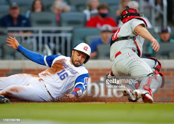 Travis d'Arnaud of the Atlanta Braves beats the tag of J.T. Realmuto of the Philadelphia Phillies to score in the first inning at Truist Park on...