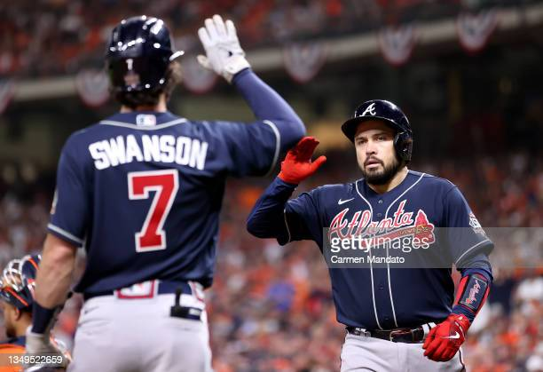Travis d'Arnaud of the Atlanta Braves is congratulated by Dansby Swanson after hitting a one run home run against the Houston Astros during the...