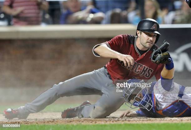 Travis d'Arnaud of the New York Mets holds the ball up to home plate umpire Ryan Additon after he tagged out AJ Pollock of the Arizona Diamondbacks...