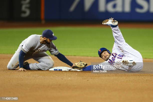 Travis d'Arnaud of the New York Mets is tagged out by Mike Moustakas of the Milwaukee Brewers trying to stretch a single into a double in the seventh...