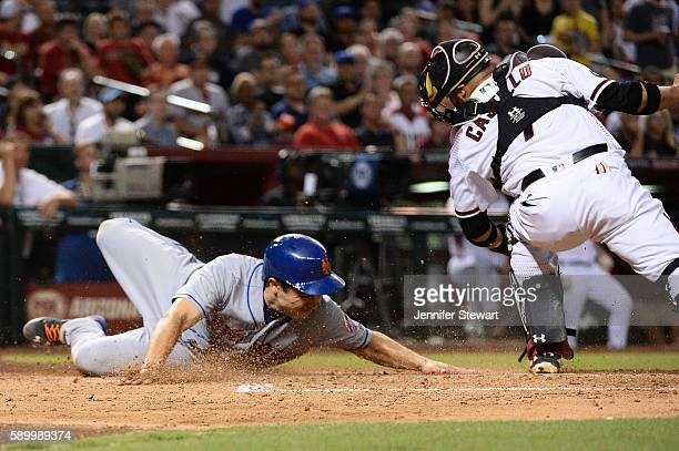 Travis d'Arnaud of the New York Mets safely slides into home plate against Welington Castillo of the Arizona Diamondbacks during the fourth inning at...