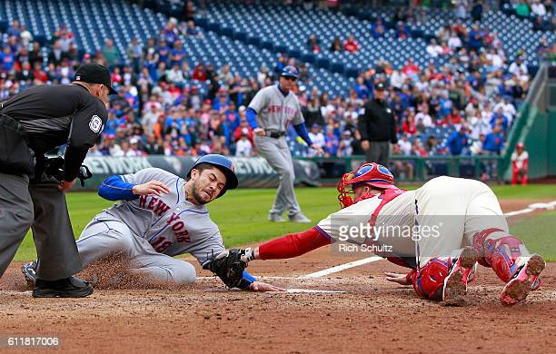 Travis d'Arnaud of the New York Mets scores before the tag of catcher Cameron Rupp of the Philadelphia Phillies on a double by Jose Reyes during the...