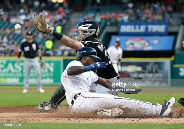 Travis Demeritte of the Detroit Tigers beats the throw to catcher James McCann of the Chicago White Sox to score from second base on a single by Jake...
