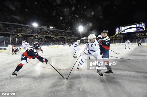 Travis Dermott of the Toronto Maple Leafs and Michal Kempny of the Washington Capitals vie for the puck during the 2018 Coors Light NHL Stadium...