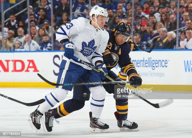 Travis Dermott of the Toronto Maple Leafs battles for position with Kyle Okposo of the Buffalo Sabres during an NHL game on March 5 2018 at KeyBank...