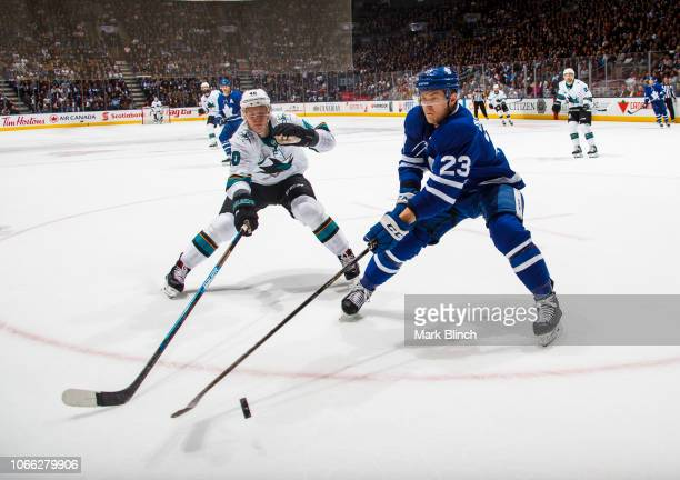 Travis Dermott of the Toronto Maple Leafs battles for the puck against Antti Suomela of the San Jose Sharks during the second period at the...