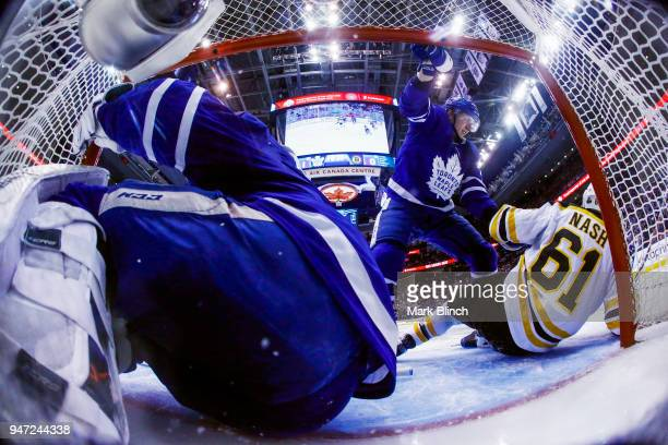 Travis Dermott of the Toronto Maple Leafs battles with Rick Nash of the Boston Bruins after he collided with Frederik Andersen of the Toronto Maple...