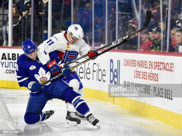 Travis Dermott of the Toronto Marlies and Daniel Carr of the Laval Rocket battle for the puck during the AHL game at Place Bell on November 1 2017 in...