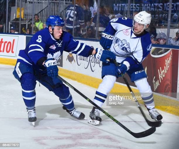 Travis Dermott of the Toronto Marlies battles in the corner with Joel Vermon of the Syracuse Crunch during game 6 action in the Division Final of the...