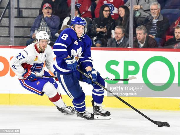 Travis Dermott of the Toronto Marlies skates the puck against Peter Holland of the Laval Rocket during the AHL game at Place Bell on November 1 2017...