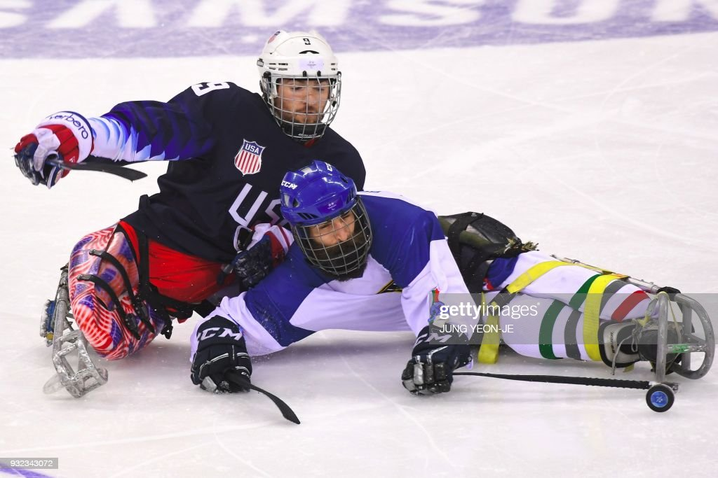 Travis Dodson of the US (L) and Eusebiu Antochi of Italy fight for the puck in the ice hockey play-off semi-final game between the US and Italy at the Gangneung Hockey Centre during the Pyeongchang 2018 Winter Paralympic Games in Gangneung on March 15, 2018. / AFP PHOTO / Jung Yeon-je