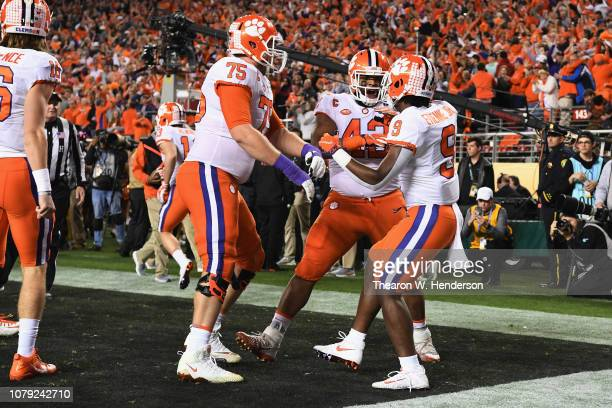 Travis Etienne of the Clemson Tigers is congratulated by his teammates after his first quarter rushing touchdown against the Alabama Crimson Tide in...