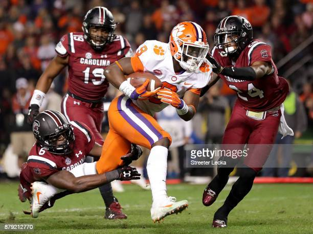 Travis Etienne of the Clemson Tigers runs for a touchdown as teammates TJ Brunson and DJ Smith of the South Carolina Gamecocks try to stop him during...