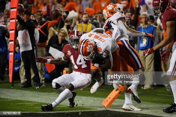 Travis Etienne of the Clemson Tigers runs the ball for a first quarter touchdown against the Alabama Crimson Tide in the CFP National Championship...