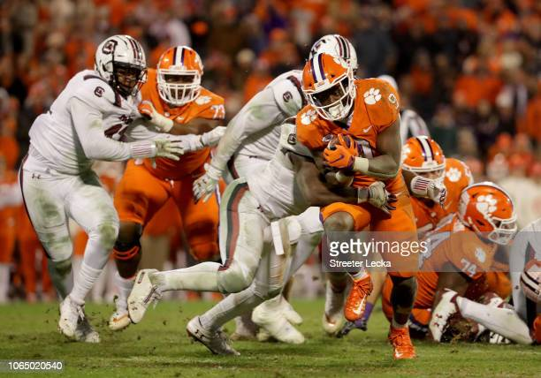 Travis Etienne of the Clemson Tigers runs with the ball against the South Carolina Gamecocks during their game at Clemson Memorial Stadium on...