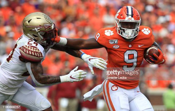 Travis Etienne of the Clemson Tigers tries to get away from Cyrus Fagan of the Florida State Seminoles during their game at Memorial Stadium on...