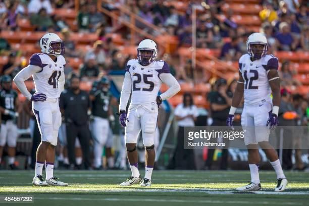 Travis Feeney, Keishawn Bierria and Dwayne Washington of the Washington Huskies are seen on field during a college football game between the...