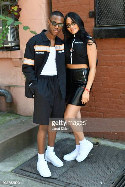 Travis Fraser is seen during July 2018 Men's Fashion week wearing Heron Preston with Deziree Gonzalez who is wearing a Palm Angels Top paired with a...