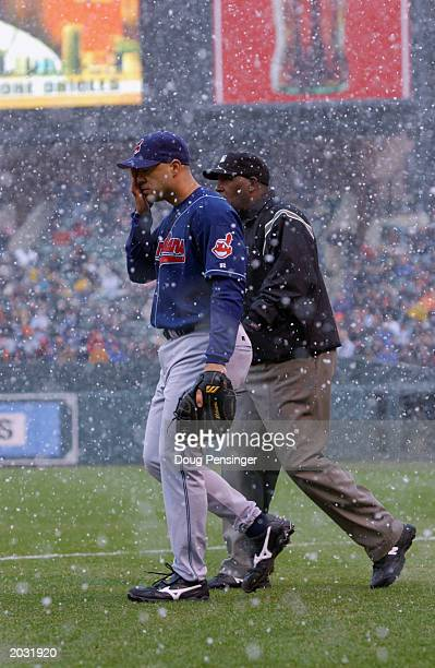 Travis Hafner of the Cleveland Indians walks back to the field with firstbase umpire Chuck Meriwether before a 13 miniute snow delay was called on...