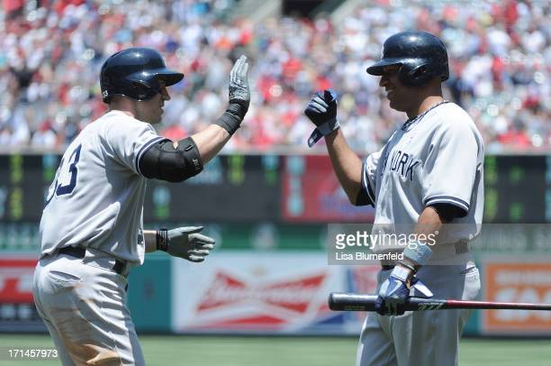 Travis Hafner of the New York Yankees celebrates with teammate Vernon Wells after scoring against the Los Angeles Angels of Anaheim at Angel Stadium...
