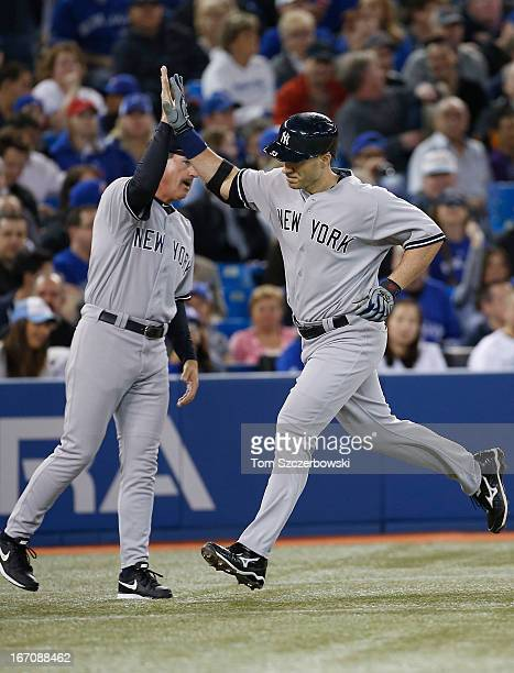 Travis Hafner of the New York Yankees is congratulated by third base coach Rob Thomson after hitting a solo home run in the third inning during MLB...