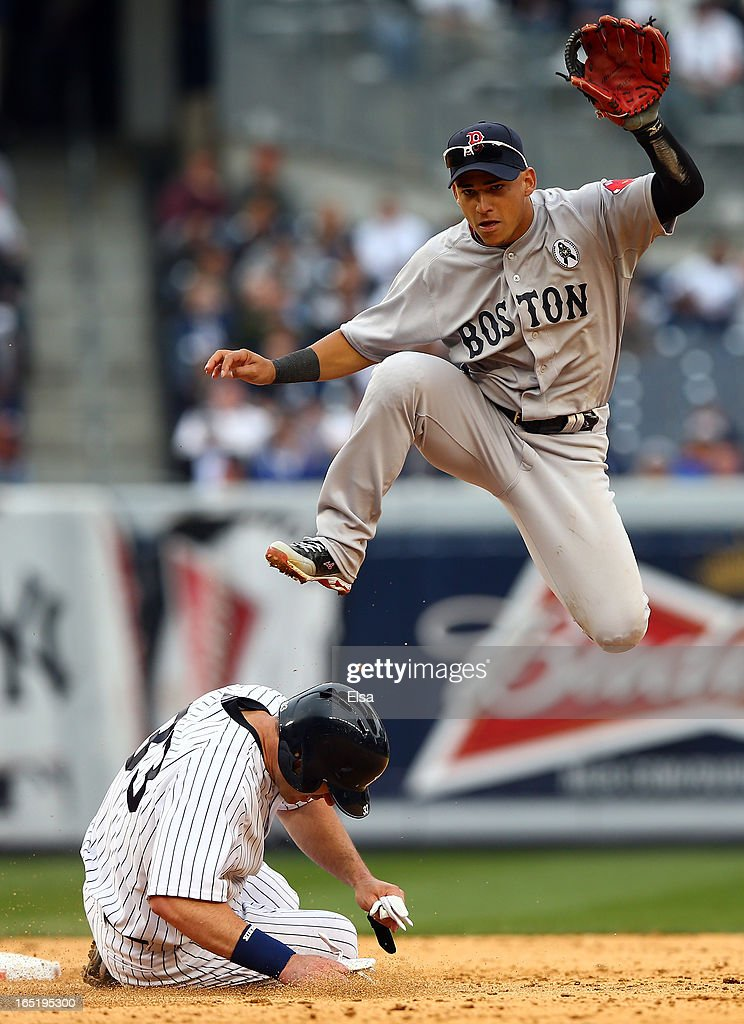 Travis Hafner #33 of the New York Yankees is out at second as Jose Iglesias #10 of the Boston Red Sox leaps over him while turning the double play during Opening Day on April 1, 2013 at Yankee Stadium in the Bronx borough of New York City.