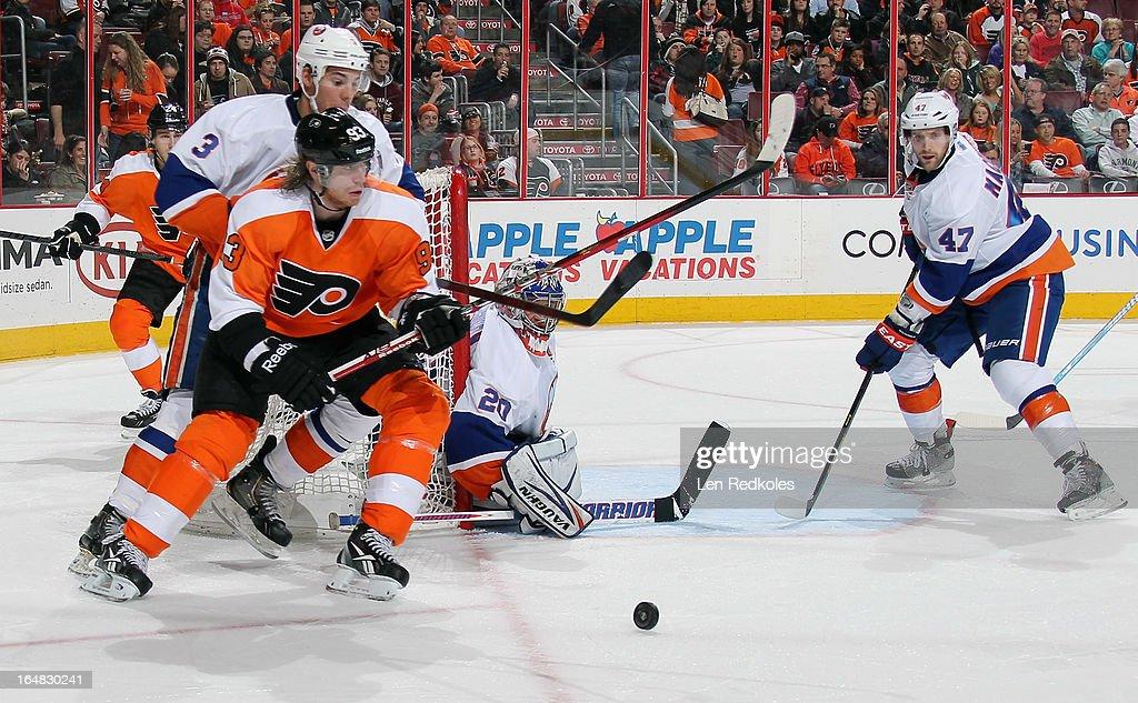 Travis Hamonic #3, Andrew MacDonald #47 and goaltender Evgeni Nabokov #20 of the New York Islanders defend against Jakub Voracek #93 of the Philadelphia Flyers on March 28, 2013 at the Wells Fargo Center in Philadelphia, Pennsylvania.