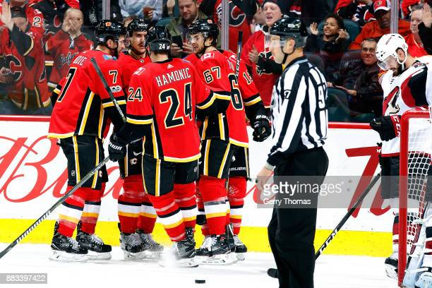 Travis Hamonic Michael Frolik and teammates of the Calgary Flames celebrate a goal against the Arizona Coyotes during an NHL game on November 30 2017...