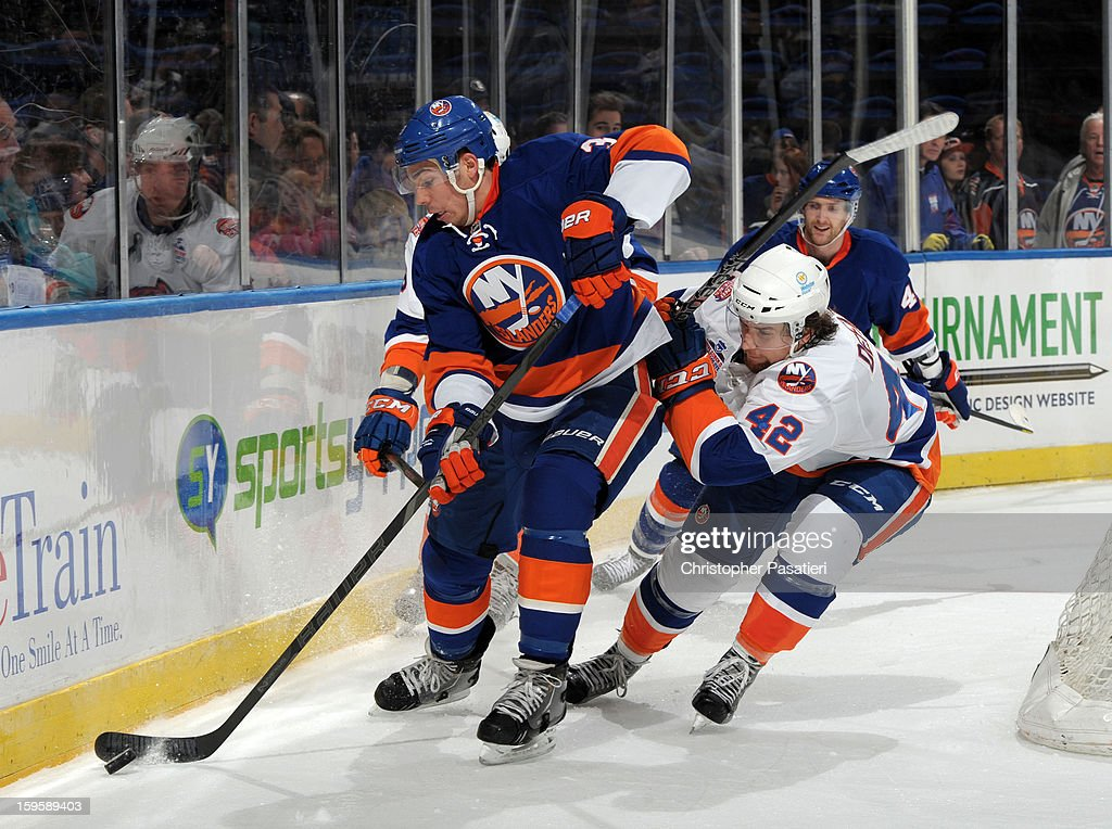 Travis Hamonic #3 of Team Blue is checked by Brandon DeFazio #42 of Team White during a scrimmage match between players of the New York Islanders and Bridgeport Sound Tigers on January 16, 2013 at Nassau Veterans Memorial Coliseum in Uniondale, New York.