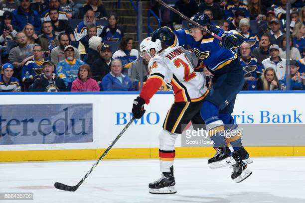 Travis Hamonic of the Calgary Flames and Beau Bennett of the St Louis Blues look for the puck at Scottrade Center on October 25 2017 in St Louis...