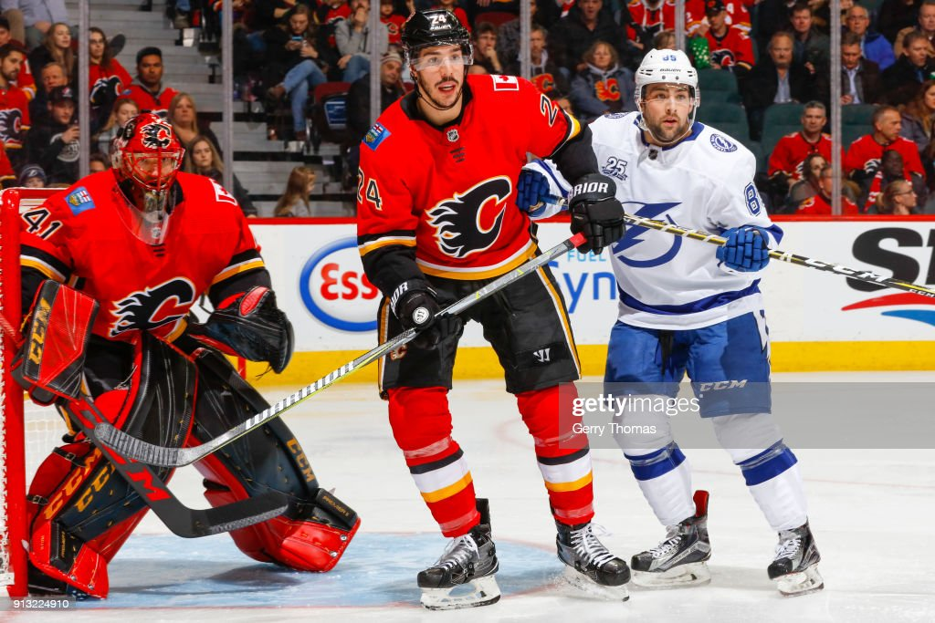Travis Hamonic #24 of the Calgary Flames and Cory Conacher #89 of the Tampa Bay Lightning battle for positionnin an NHL game on February 1, 2018 at the Scotiabank Saddledome in Calgary, Alberta, Canada.