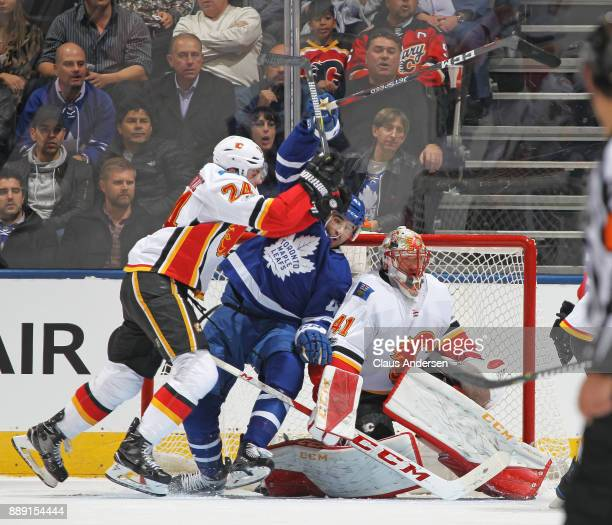 Travis Hamonic of the Calgary Flames battles against Nazem Kadri of the Toronto Maple Leafs during an NHL game at the Air Canada Centre on December 6...