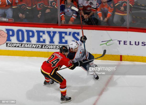 Travis Hamonic of the Calgary Flames battles against the Edmonton Oilers at Scotiabank Saddledome on March 13 2018 in Calgary Alberta Canada