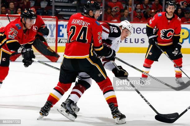 Travis Hamonic of the Calgary Flames checks Christian Dvorak of the Arizona Coyotes during an NHL game on November 30 2017 at the Scotiabank...