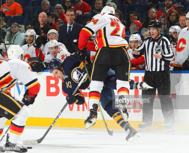 Travis Hamonic of the Calgary Flames checks Seth Griffith of the Buffalo Sabres during the third period of an NHL game on March 7 2018 at KeyBank...