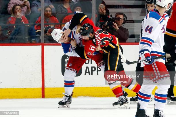 Travis Hamonic of the Calgary Flames fights Chris Kreider of the New York Rangers during an NHL game on March 2 2018 at the Scotiabank Saddledome in...