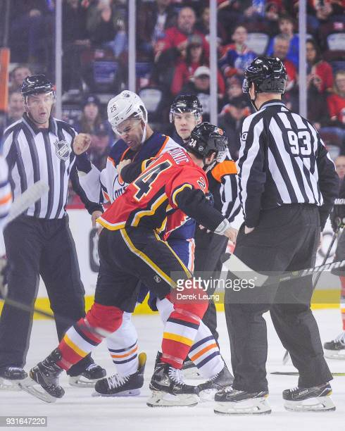 Travis Hamonic of the Calgary Flames fights Darnell Nurse of the Edmonton Oilers during an NHL game at Scotiabank Saddledome on March 13 2018 in...