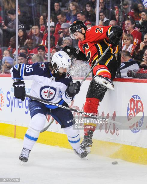 Travis Hamonic of the Calgary Flames gets checked by Mathieu Perreault of the Winnipeg Jets during an NHL game at Scotiabank Saddledome on January 20...