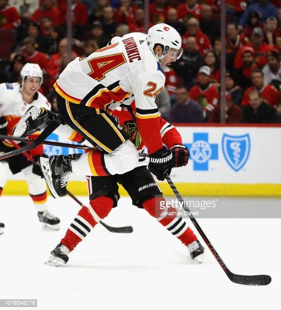 Travis Hamonic of the Calgary Flames leaps out of the way of the puck against the Chicago Blackhawks at the United Center on December 02, 2018 in...