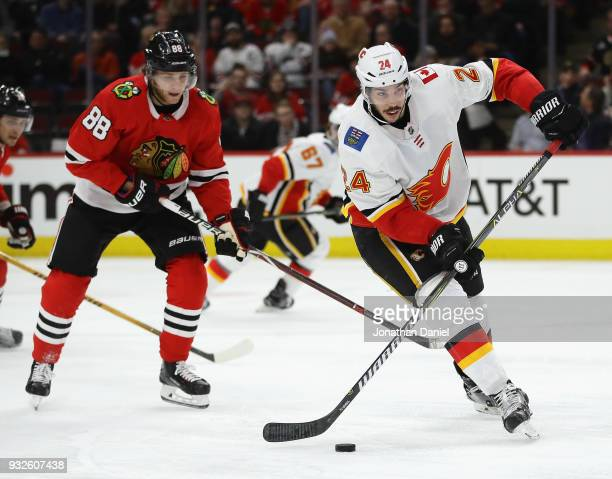 Travis Hamonic of the Calgary Flames looks to pass in front of Patrick Kane of the Chicago Blackhawks at the United Center on February 6 2018 in...