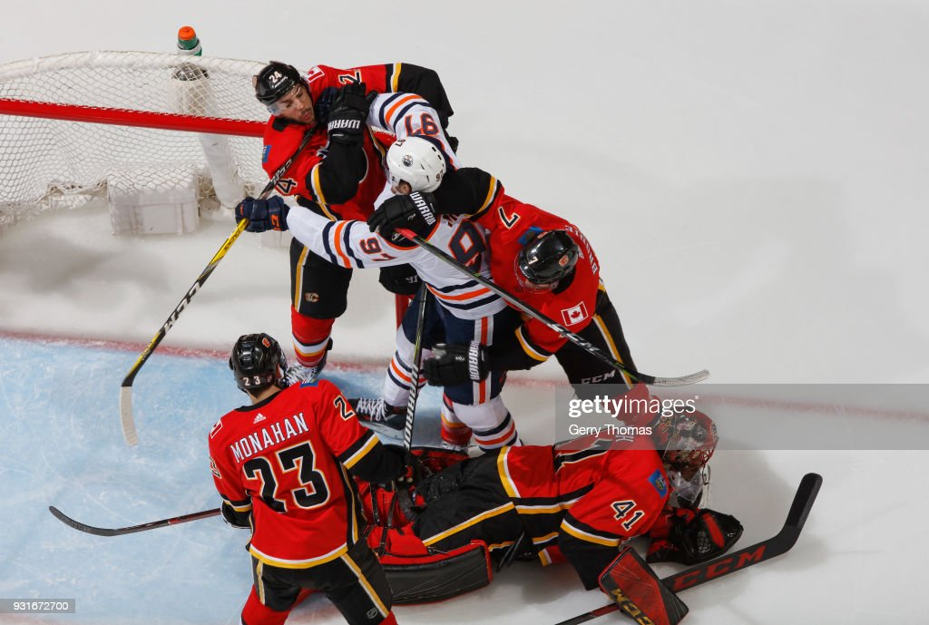 Travis Hamonic #24 of the Calgary Flames mixes it up against Connor McDavid #97 of the Edmonton Oilers at Scotiabank Saddledome on March 13, 2018 in Calgary, Alberta, Canada.