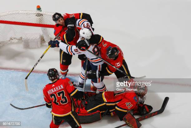 Travis Hamonic of the Calgary Flames mixes it up against Connor McDavid of the Edmonton Oilers at Scotiabank Saddledome on March 13 2018 in Calgary...