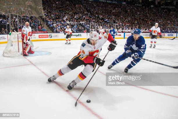 Travis Hamonic of the Calgary Flames skates against James van Riemsdyk of the Toronto Maple Leafs during the first period at the Air Canada Centre on...