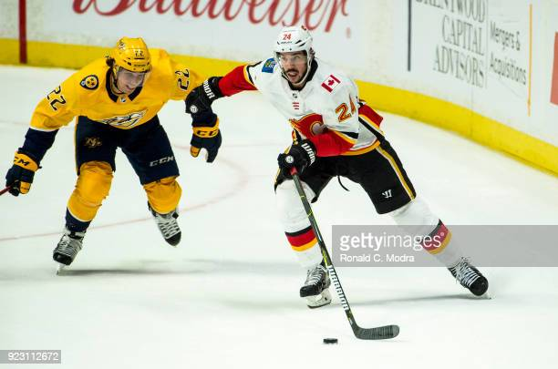 Travis Hamonic of the Calgary Flames skates against Kevin Fiala of the Nashville Predators during an NHL game at Bridgestone Arena on February 15...