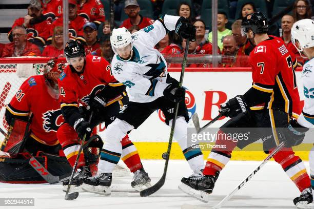 Travis Hamonic of the Calgary Flames skates against Melker Karlsson of the San Jose Sharks during an NHL game on March 16 2018 at the Scotiabank...